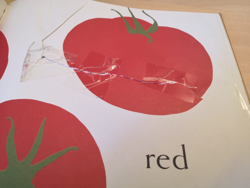 Page with tomatoes repaired by children with tape.